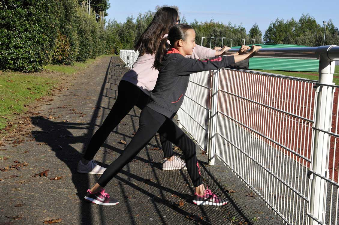 S'étirer grâce à la main courante le long de la piste d'athlétisme